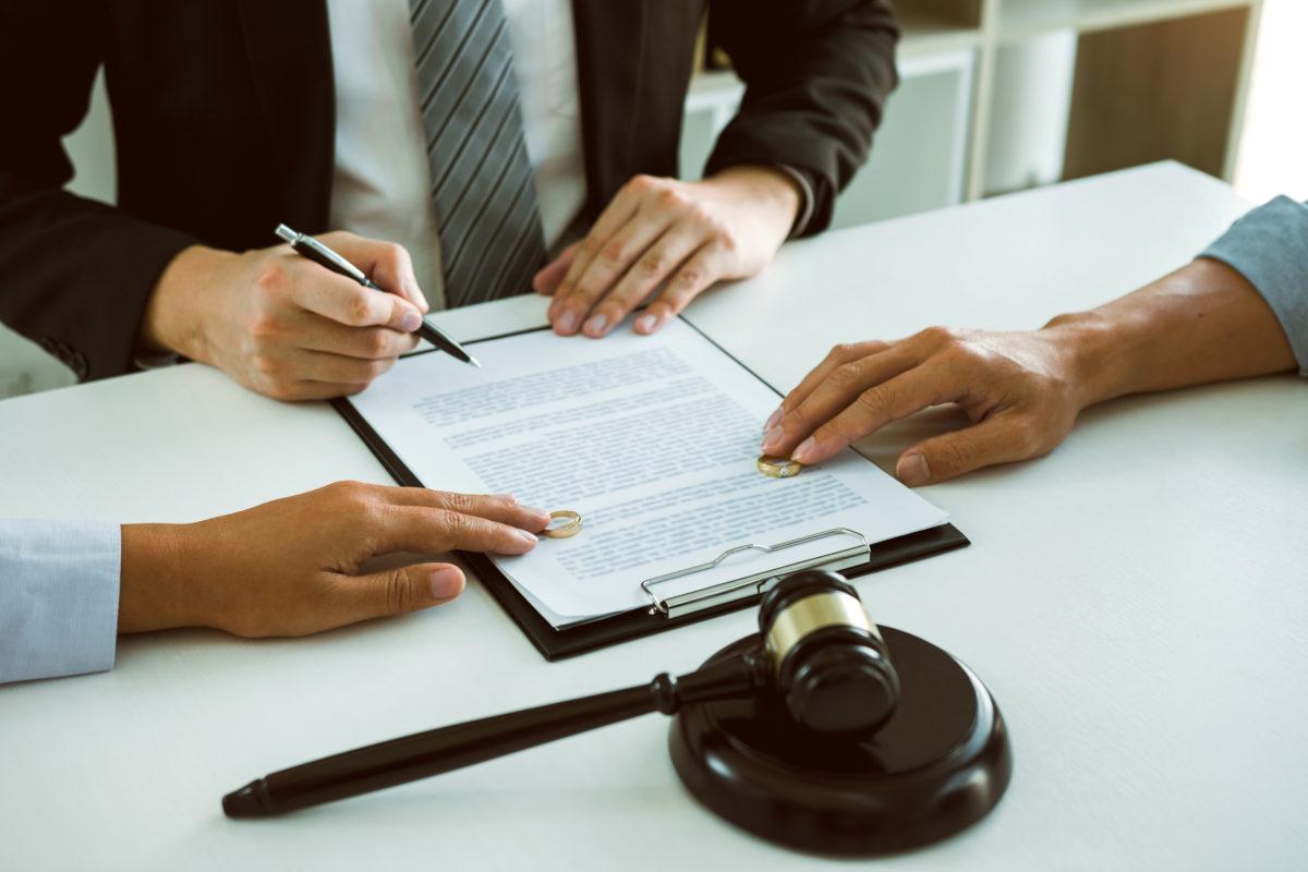 manos de pareja y abogado sobre un documento