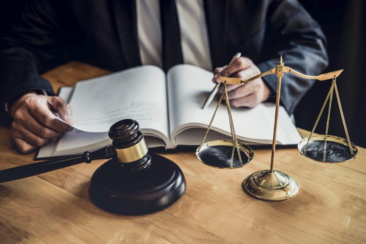 manos, balanza, mazo jurídico y cuaderno