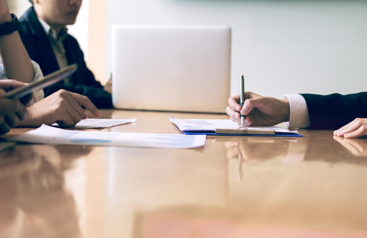 manos firmando recursos sobre una mesa