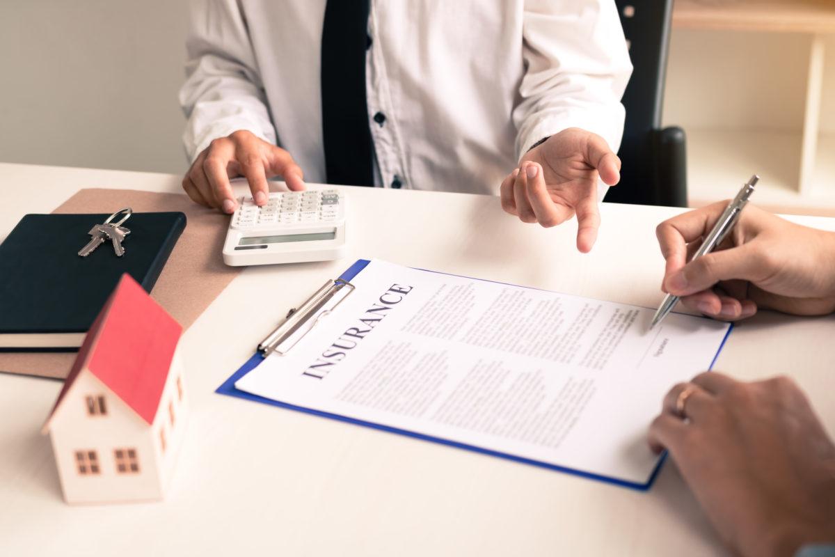manos sobre un contrato y una casita